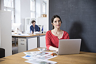 Woman using laptop on table in office thinking - FKF02280