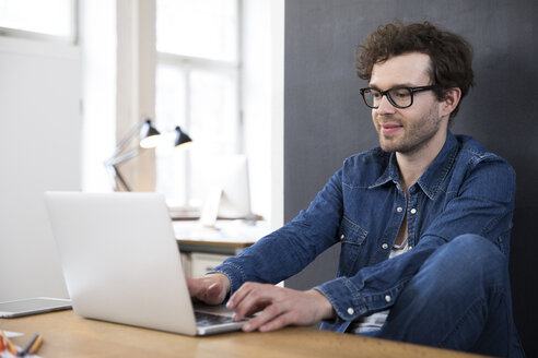 Smiling man using laptop in office - FKF02283