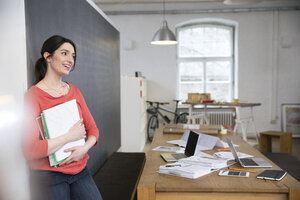 Smiling woman holding documents at desk in office - FKF02289