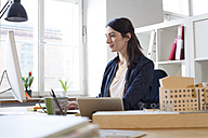 Woman working at desk in office - FKF02298