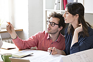 Man and woman discussing at desk in office - FKF02307