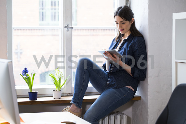 Woman using tablet at the window in office - FKF02313 - Florian Küttler/Westend61
