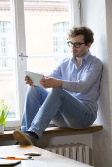 Man using tablet at the window in office - FKF02316