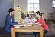 Man and woman working on project in office together - FKF02328