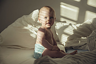 Baby boy sitting in bed in shadow and sunlight - MFF03524