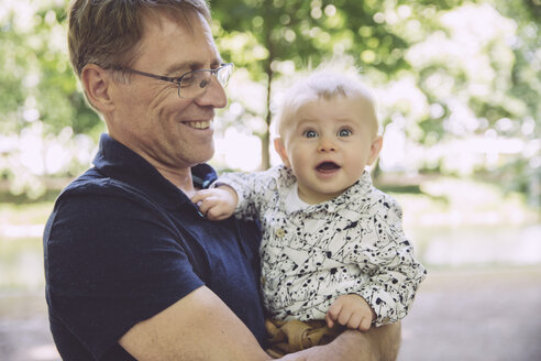 Smiling father holding amazed baby boy outdoors - MFF03527