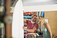 Surfboard shaper workshop, happy man and woman with surfboard - ZEF13674