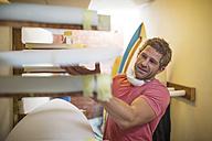 Surfboard shaper workshop, man checking quality of surfboard - ZEF13677