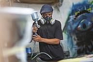 Surfboard shaper workshop, surfboard shop employee spraying surfboard - ZEF13680