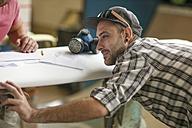 Surfboard shaper workshop, man checking quality of surfboard - ZEF13683