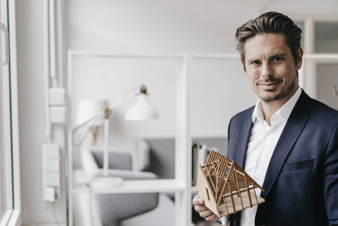 Confident architect holding architectural model - KNSF01266