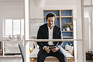 Businessman with tablet and headphones sitting on table - KNSF01287