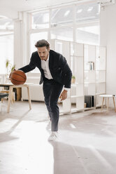 Businessman playing basketball in office - KNSF01293