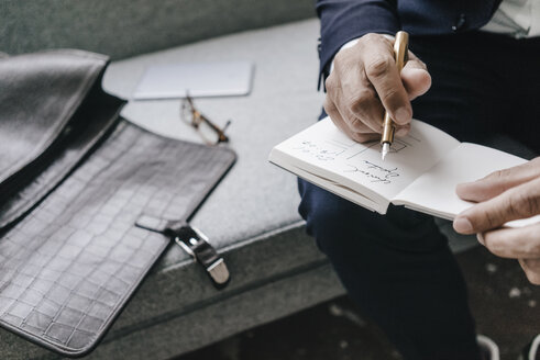 Close-up of businessman writing and drawing in notebook - KNSF01305