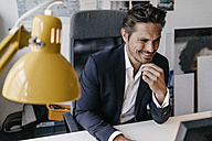 Smiling businessman working at desk - KNSF01311