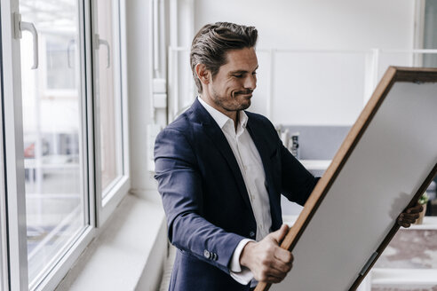Businessman holding picture frame - KNSF01314