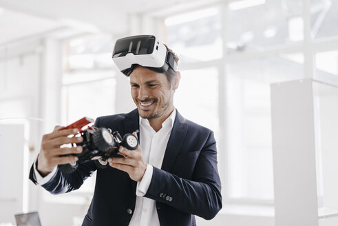 Smiling businessman wearing VR glasses looking at toy racing car - KNSF01335