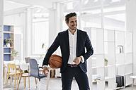 Businessman holding basketball in office - KNSF01338
