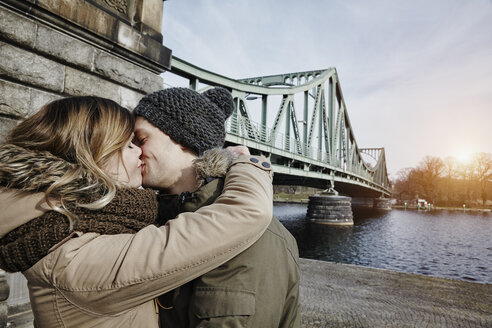 Germany, Potsdam, young couple kissing at Glienicke Bridge - ANHF00026