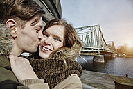 Germany, Potsdam, young couple kissing at Glienicke Bridge - ANHF00032