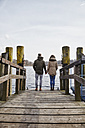 Germany, Potsdam, rear view of young couple standing on jetty at Havel River - ANHF00035