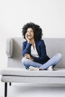 Young businesswoman sitting on couch, being happy - KNSF01351