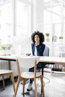 Young businesswoman sitting at her desk - KNSF01354