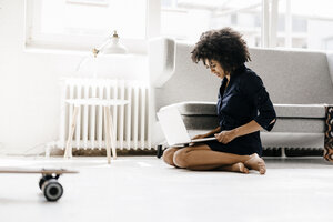 Young woman sitting on floor, using laptop - KNSF01360