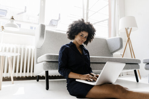 Young woman sitting on floor, using laptop - KNSF01363