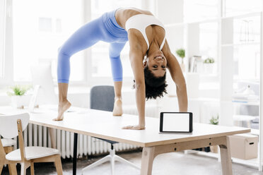 Young woman practising yoga with laptop by her side - KNSF01396