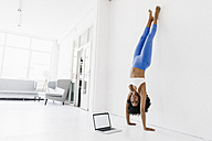Young woman practising yoga with laptop by her side - KNSF01408