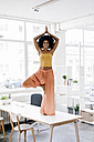 Young woman doing yoga on her desk - KNSF01420