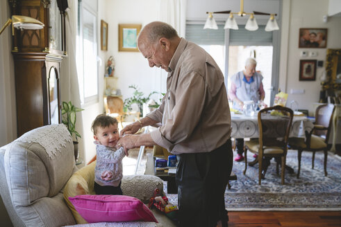Great-grandfather taking care of a baby girl at home - GEMF01622