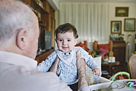 Great-grandfather holding a cute baby girl at home - GEMF01625