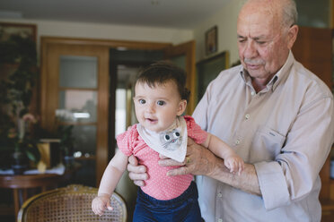 Happy Baby girl standing with help of Great-grandfather at home - GEMF01628
