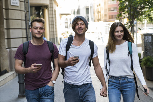 Friends with cell phones walking in the city - KKAF00832