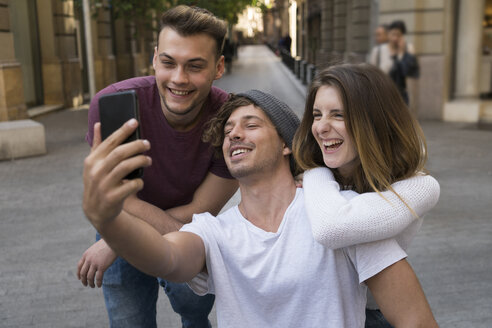Three happy friends taking a cell phone selfie in the city - KKAF00853