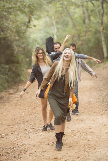 Four happy friends having fun on path in the forest - ZOCF00380