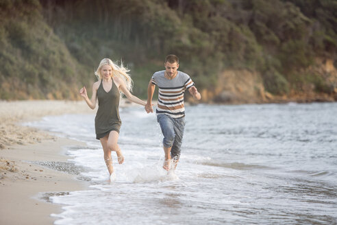 Happy couple running at the beach - ZOCF00389
