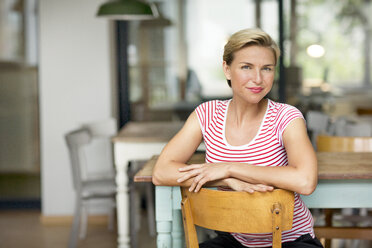 Portrait of confident blond woman sitting on chair - PESF00583