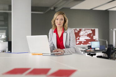 Portrait of confident businesswoman using laptop in office - PESF00586