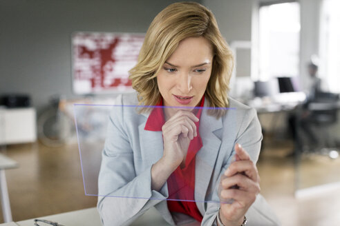 Businesswoman using futuristic portable device - PESF00589
