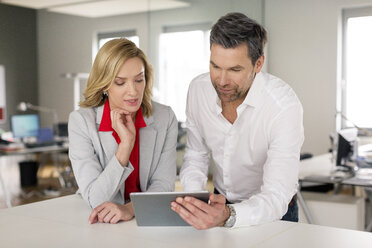 Businessman and businesswoman using tablet together - PESF00592