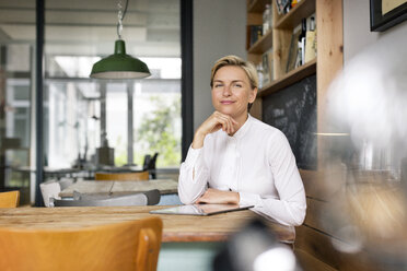 Portrait of confident blond woman sitting at table - PESF00598