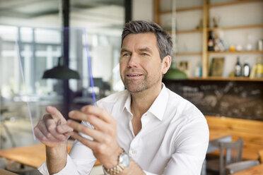 Businessman using futuristic portable device - PESF00607