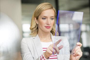 Businesswoman using futuristic portable device - PESF00616