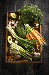 Various organic vegetables on dark wooden tray - MAEF12210