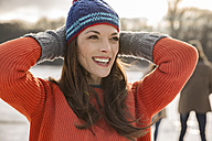 Happy woman holding her woolen hat - MFF03537