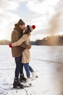 Couple with ice skates kissing on frozen lake - MFF03540