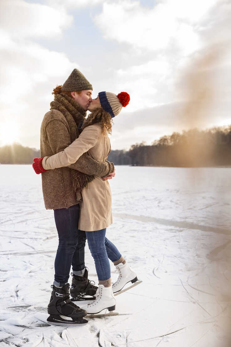 Couple with ice skates kissing on frozen lake - MFF03540 - Mareen Fischinger/Westend61